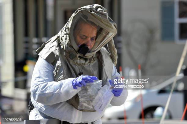 A nurse in a hazmat suit packages a completed test for Coronavirus Covid19 to be sent to a lab at Somerville Hospital in Somerville Massachusetts on...