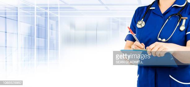 nurse in blue uniform writing - nhs staff stock pictures, royalty-free photos & images