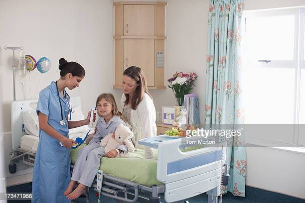 nurse in children's hospital with girl patient and mother - girl in hospital bed sick stock photos and pictures