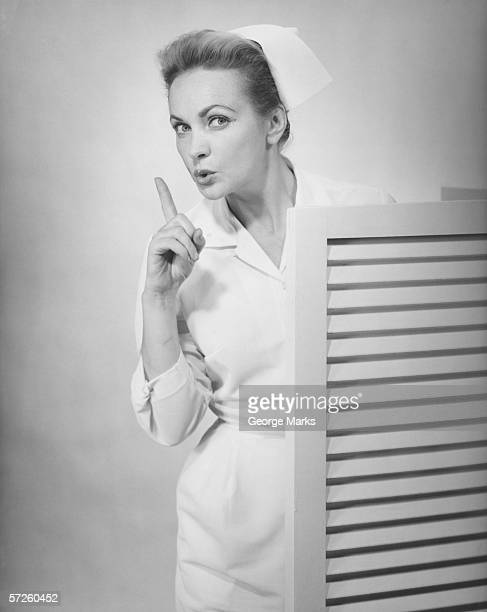 Nurse in consulting room showing hush gesture, (B&W)