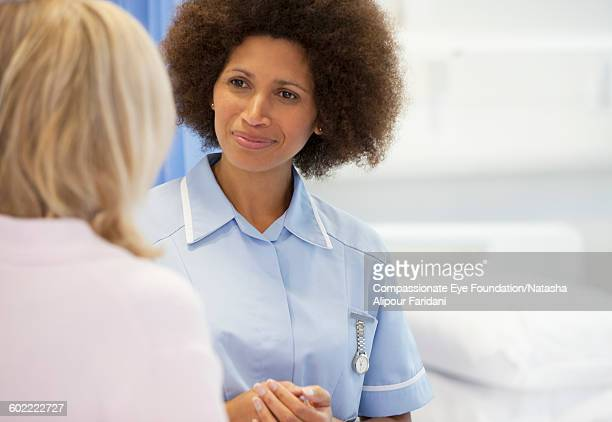 Nurse in discussion with patient in hospital