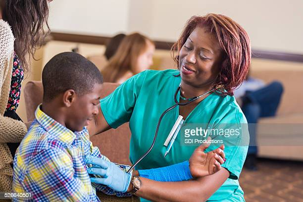 Nurse in emergency room checking on young boy with injury