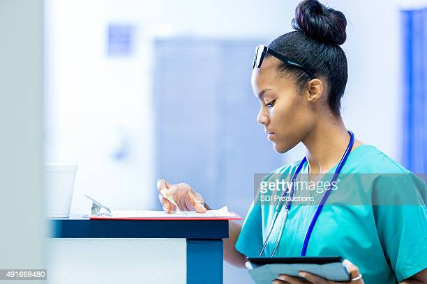 Nurse in hospital checking patient charts during rounds