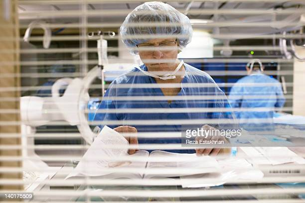Nurse in surgery checks medical book
