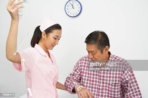 Nurse injecting to an old man.
