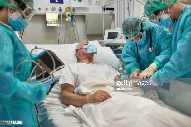 nurse inserting iv into arm of senior male covid-19 patient - iv drip stock pictures, royalty-free photos & images
