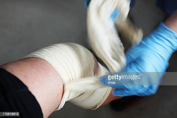 nurse is changing bandage to a wounded patient's knee - bloody leg stock photos and pictures