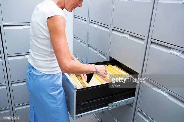 Nurse is checking card index of patients in file cabinet