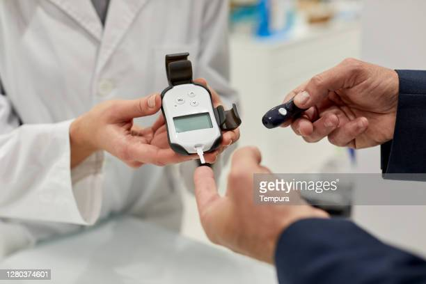 a nurse is doing a diabetes sugar test on a patient - glycemia stock pictures, royalty-free photos & images
