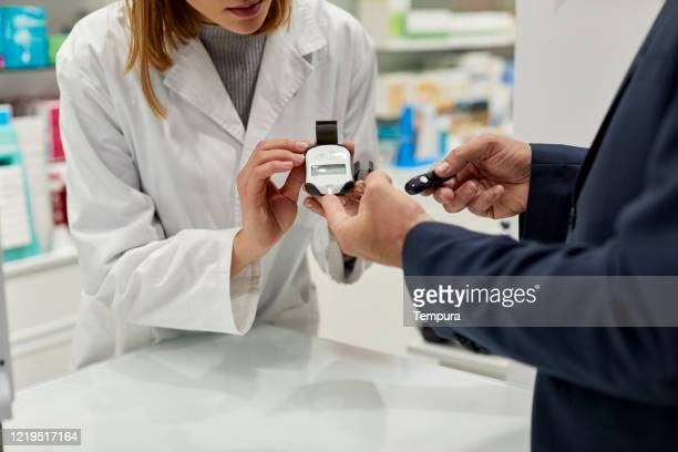 a nurse is doing a diabetes sugar test to a patient. - glycemia stock pictures, royalty-free photos & images