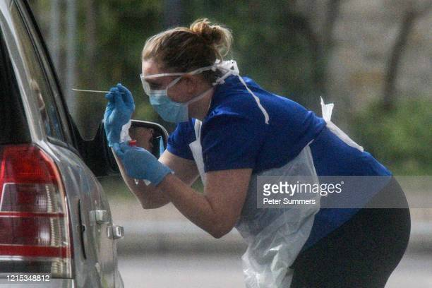 A nurse is seen swabbing the occupants of a car at a drive through COVID19 testing station at Chessington World Of Adventures Resort on March 28 2020...