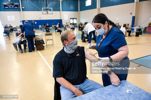 Nurse Jannell Schera prepares to give Scott Melot, of Hamburg, a dose of COVID-19 vaccine. At the Olivet Boys and Girls Club Pendora site in Reading,...