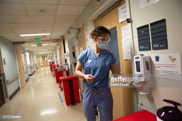 Nurse Karen Hayes cleans her hands with sanitizer after tending to a patient who has COVID19 in the acute care COVID unit at Harborview Medical...