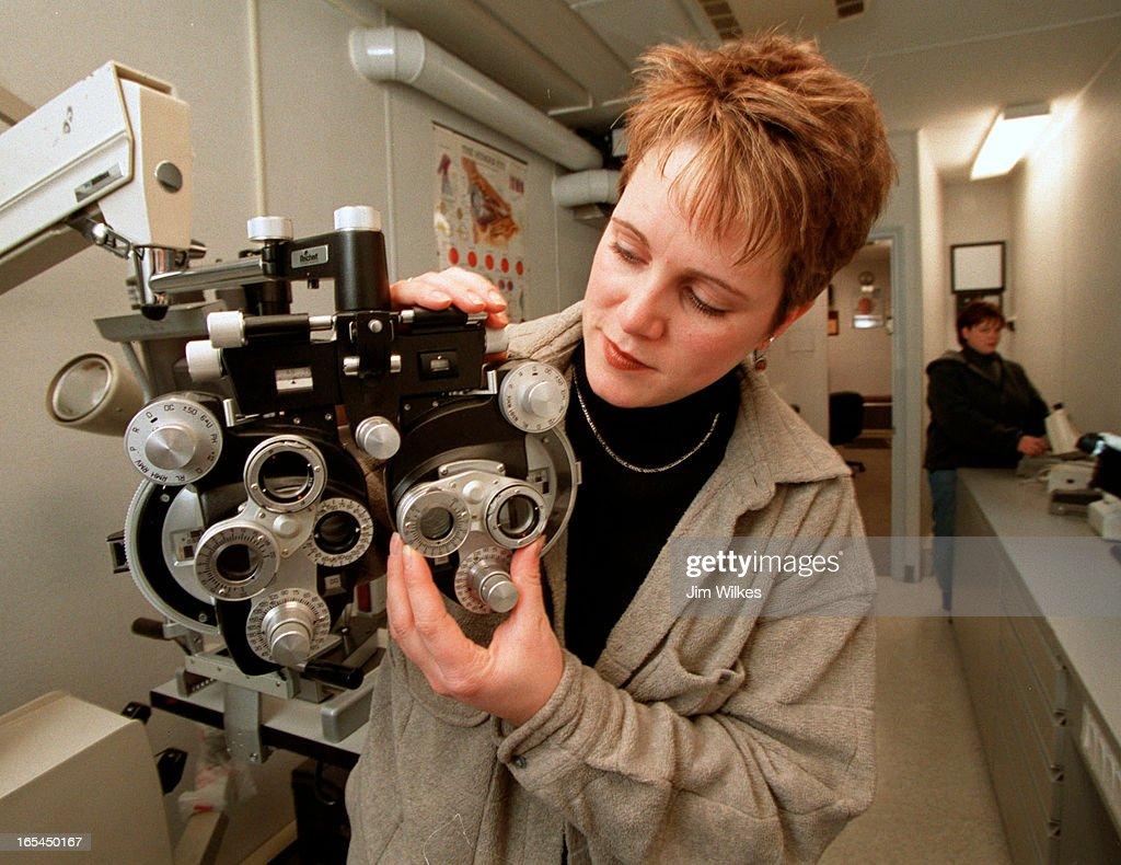 Nurse Kate Neil checks out eye examination equipment in foreground
