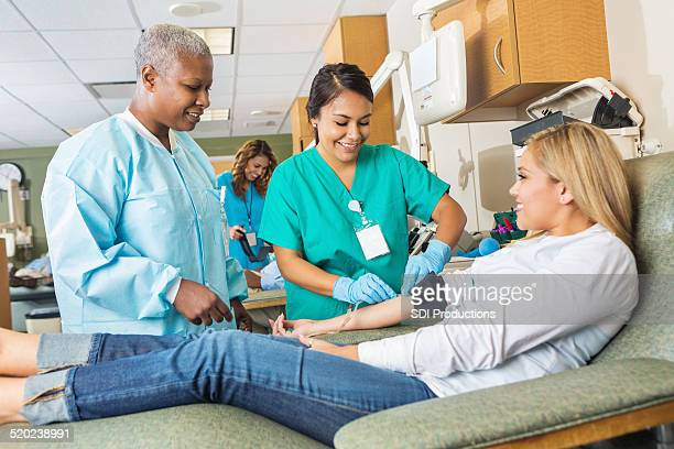 nurse learning to assist patient donating blood in hospital - blood donation stock pictures, royalty-free photos & images