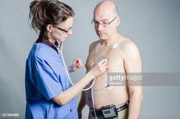nurse listening man's heart while wearing holter monitor - holter monitor stock photos and pictures