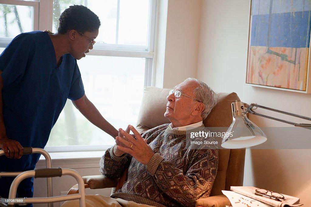 Nurse looking after senior man at home : Stock Photo
