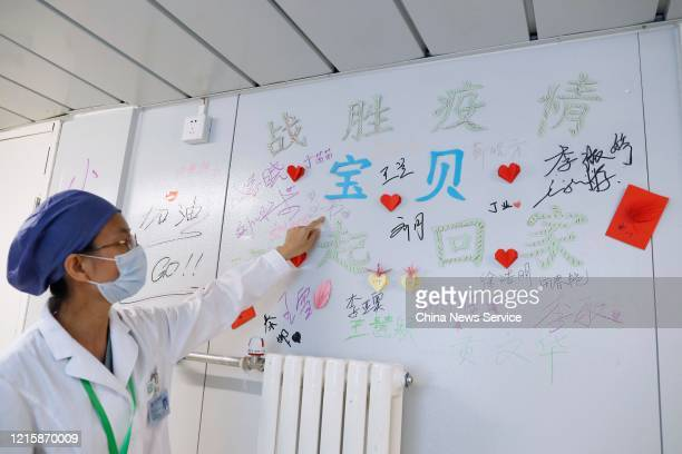A nurse looks at a wall marked by signatures at 'Clean Zone' which does not receive patients in Xiaotangshan Hospital on March 30 2020 in Beijing...