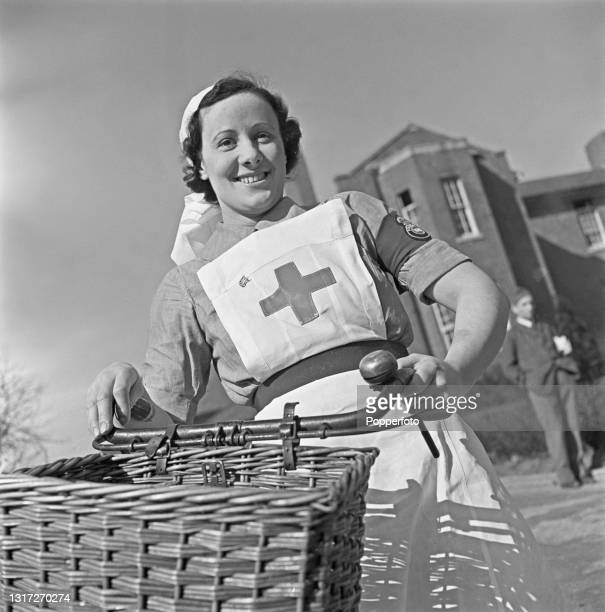 Nurse M S Sparkes uses a bicycle to cycle through the grounds to her ward at Shenley Hospital, a military hospital at Shenley near St Albans in...