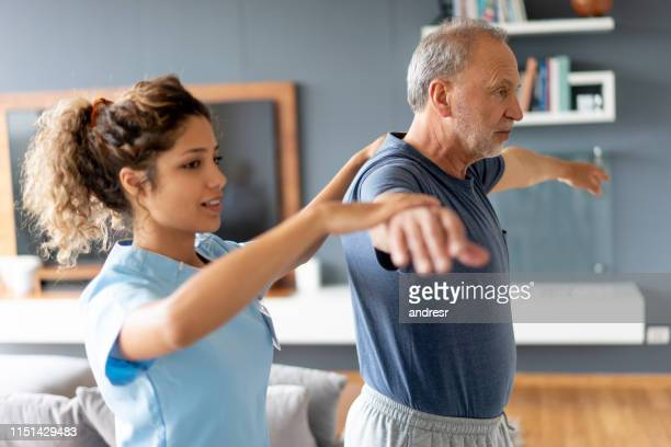 nurse making a house visit to a senior patient - shoulder stock pictures, royalty-free photos & images