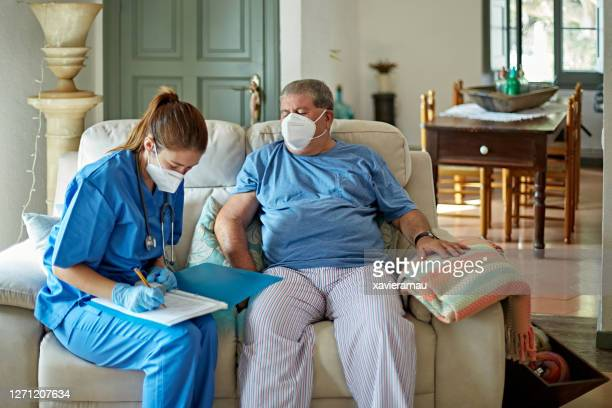 nurse making house call to care for senior man in recovery - two seater sofa stock pictures, royalty-free photos & images