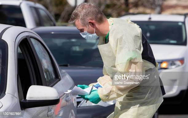 Nurse manager Cullen Anderson, RN, screens people in a line of cars waiting to be tested for coronavirus COVID-19 at a drive-thru testing station at...