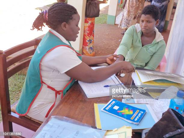 Nurse Margret Nanyonga cares for an HIV positive patient in the health center in Kyetume Uganda 28 October 2014 He has been living with HIV since...