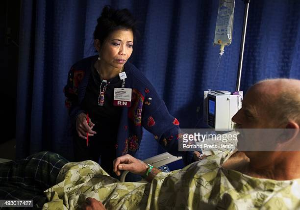 Nurse Marieta Atienza cares for a patient who just emerged from surgery shortly before sunrise December 12 at Maine Medical Center in Portland...