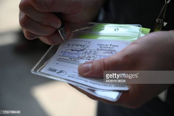 """Nurse marks a coronavirus vaccination card with a third """"booster"""" dose of the Pfizer Covid-19 vaccine at a vaccine clinic hosted by The Tournament of..."""