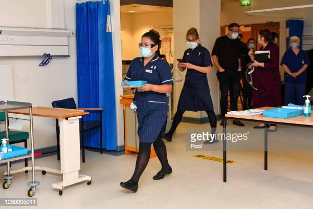 Nurse May Parsons carries the first Pfizer/BioNTech covid-19 vaccine at University Hospital Coventry, to be administered to Margaret Keenan at the...