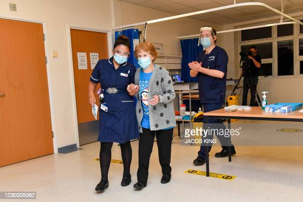 Nurse May Parsons walks with Margaret Keenan at University Hospital in Coventry, central England, on December 8, 2020 as Keenan is prepared to...