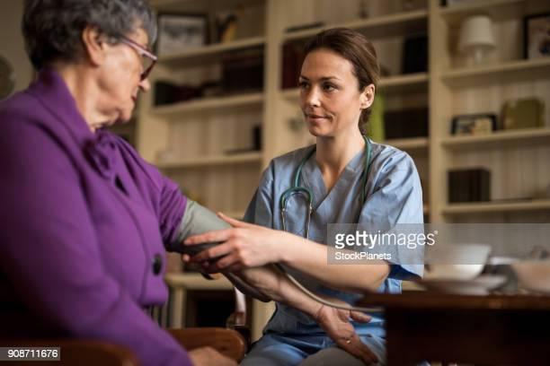 verpleegkundige maatregel druk senior vrouwen - dokterspraktijk stockfoto's en -beelden