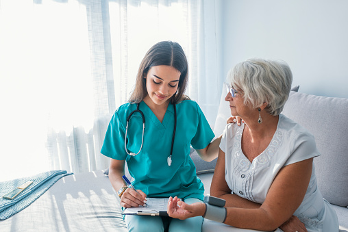 Nurse measuring blood pressure of senior woman at home 1034253530