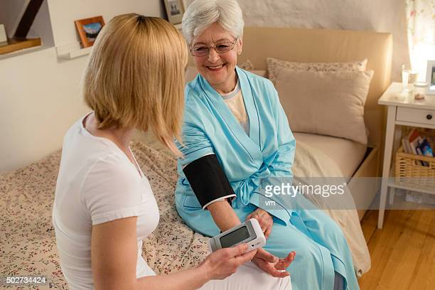 Nurse measuring blood pressure of senior woman