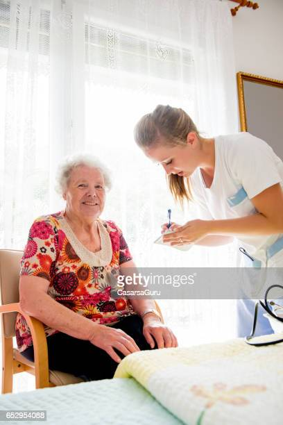 nurse measuring blood pressure to a senior woman in the nursery home - residential care stock photos and pictures