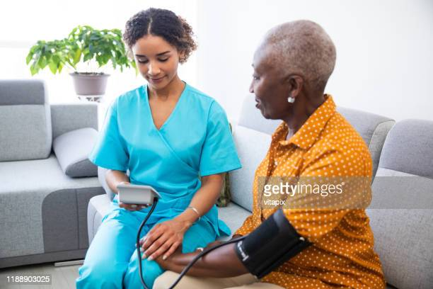 nurse measuring patient's blood pressure - hospice stock pictures, royalty-free photos & images