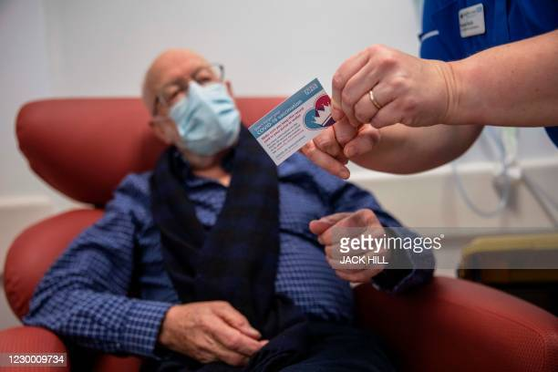 Nurse Naomi Walsh shows Roger Shaw his vaccination card after as he receives the Pfizer-BioNTech Covid-19 vaccine at the Royal Free hospital in...