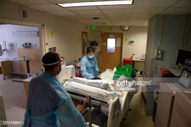 Nurse Nick Brideau from the ICU COVID unit wheels a patient towards Nurse Karen Hayes as the patient is transferred to the acute care COVID unit at...