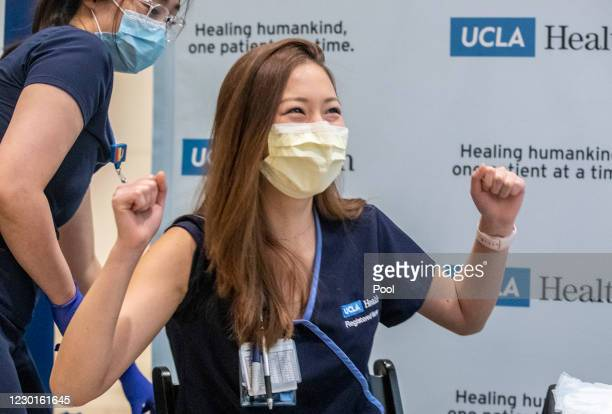 Nurse Nicole Chang celebrates after receiving one of the first injections of the COVID-19 vaccine at Ronald Reagan UCLA Medical Center on December...
