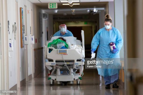 A nurse on infection control accompanies a patient being transferred from the ICU COVID unit to the acute care COVID unit at Harborview Medical...