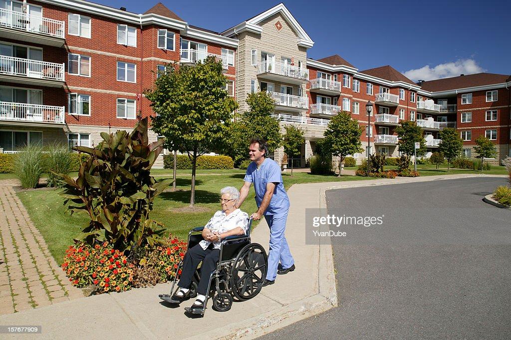 nurse or doctor pushing a wheelchair outdoors : Stock Photo
