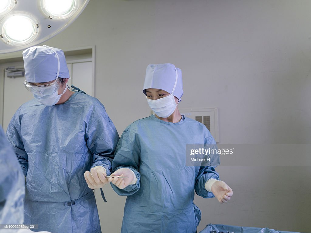 Nurse passing forceps to doctor during operation : Foto stock