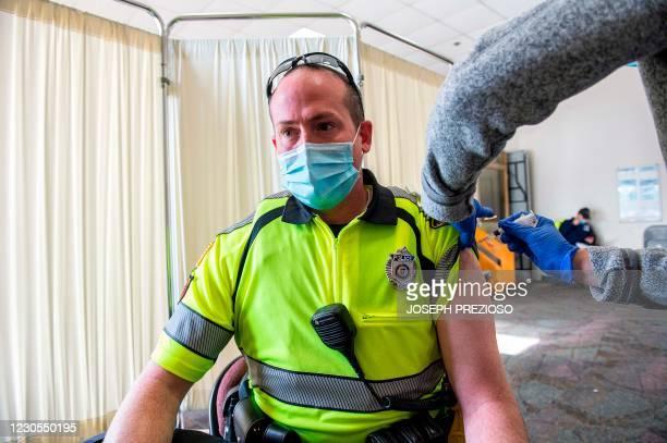 Nurse Patti Ward inoculates Marlborough Police Officer Andrew Larose with the Moderna Covid-19 vaccine at UMass Memorial Hospital in Marlborough,...