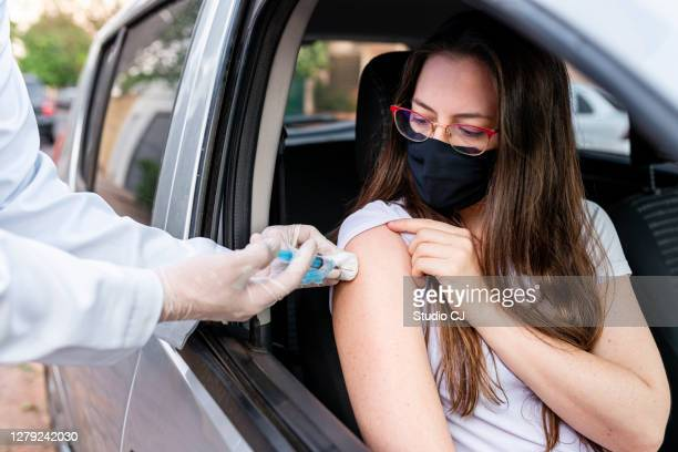 nurse performing drive-thru immunization - covid 19 vaccine stock pictures, royalty-free photos & images
