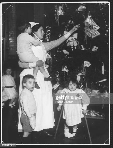 A nurse picks a gift from the tree for a little boy at a Christmas party at Great Ormond Street Hospital