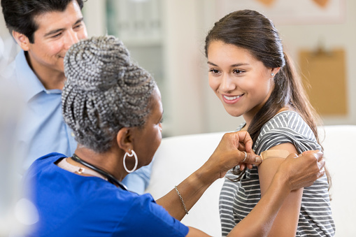 Nurse places bandage on female patient 1053526764
