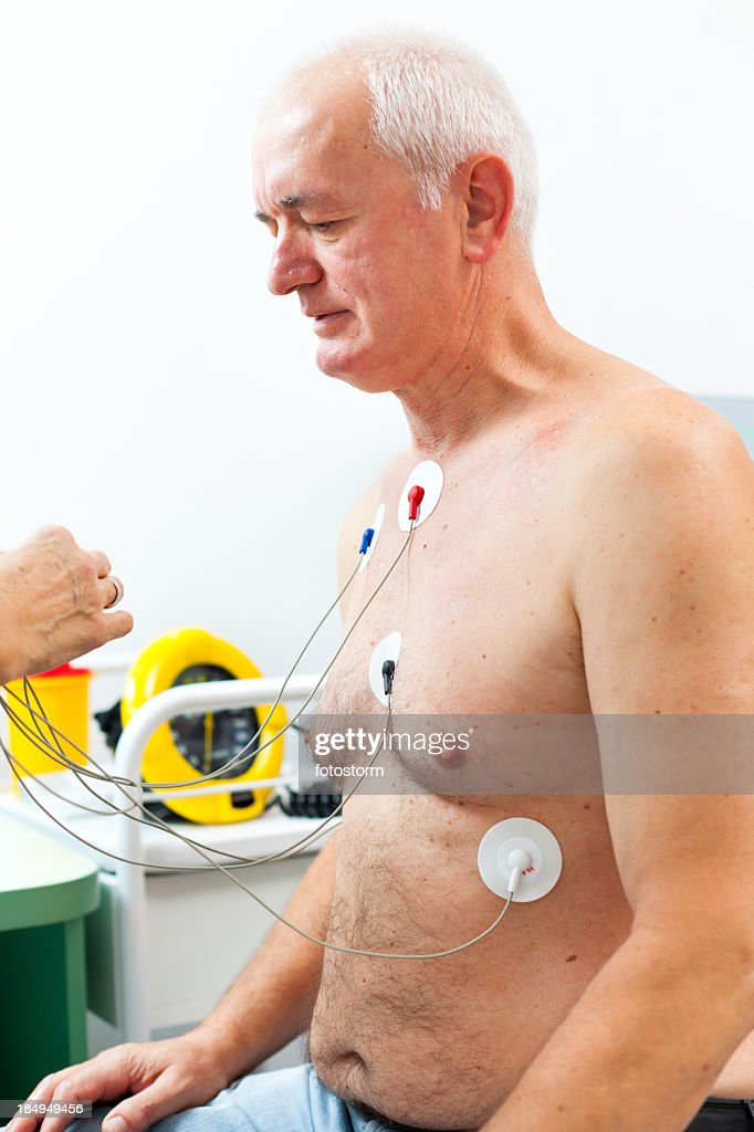 Nurse placing Holter monitor on patient's chest : Stock Photo