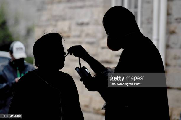 Nurse practitioner Daniel Lucas-Neel II checks the temperature of a man who asked to be screened at a pop-up Coronavirus testing site run by a free...