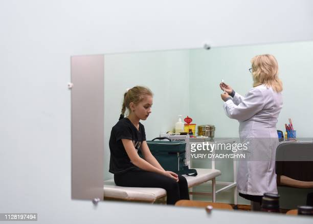 A nurse prepares a measles vaccine to a girl in the school of Lapaivka village near the western Ukrainian city of Lviv on February 21 2019 The mobile...