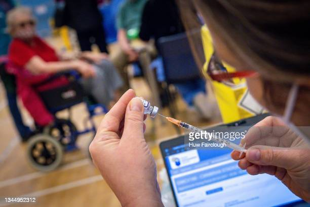 Nurse prepares a syringe ready to administer a vaccine on October 05, 2021 in Cwmbran, Wales. Patients who attend the vaccine centre are also being...